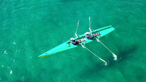 Aerial drone bird's eye view video of sport canoe operated by 2 young women in emerald tropical clear waters
