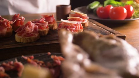 The work of a professional chef for the preparation of traditional Spanish tapas. Unfolding cheese plates on a layer of tomato and bacon.