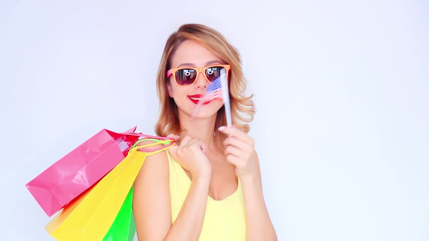 Young redhead girl with shopping bags and USA flag on white background   Shutterstock HD Video #1010180261