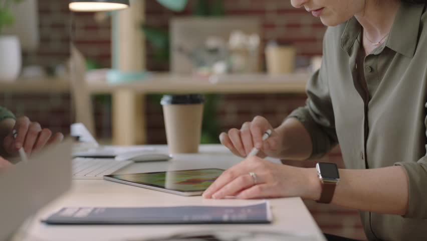 Young business woman graphic designer using tablet pc drawing on touch screen device brainstorming creative designs for corporate project deadline | Shutterstock HD Video #1010188781