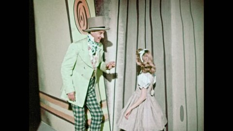 1950s: Mad Hatter speaks with girl. Mad Hatter invites Jabberwocky from behind Alice in Wonderland book. Jabberwocky bows at little girl.