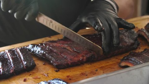 Close-up of a professional cutting BBQ ribs for serving.