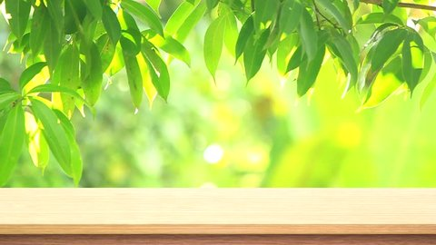 Wood table top on green leaves with bokeh background.