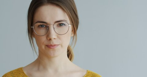Portrait of the beautiful woman in glasses and with long fair hair looking straight in the camera seriously and then smiling cheerfully on the white wall background. Close up. Indoors