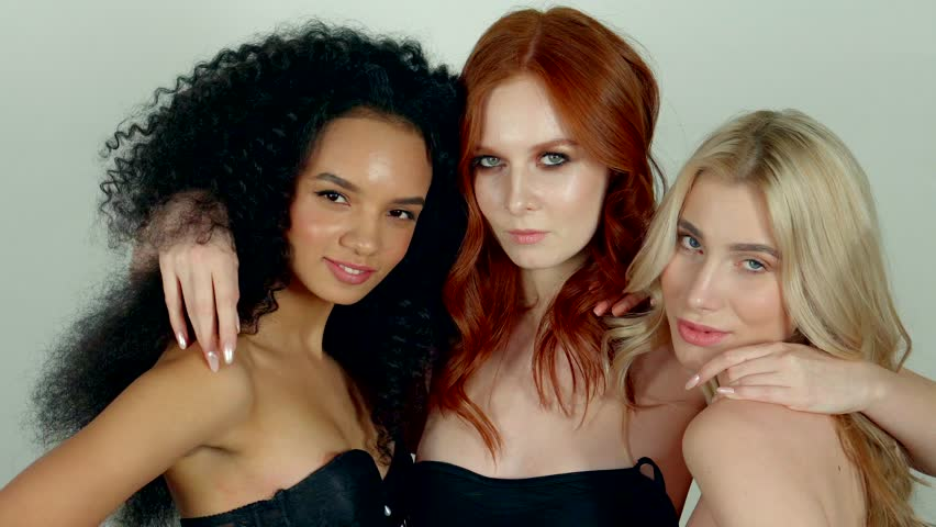 Three slim graceful women are posing for a camera and embracing. Redhead girl is hugging her friends and touching their long black and blonde hair