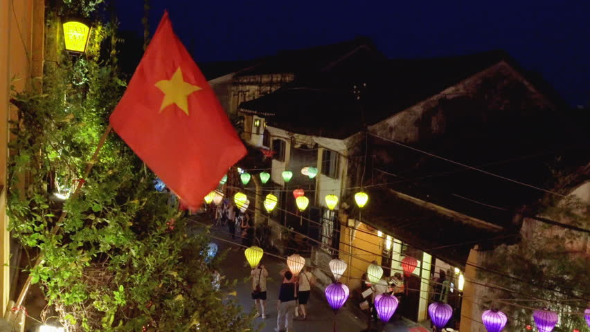Hoi An (Hoian), Vietnam - April 11, 2018: The flag of Vietnam (red flag with a gold star) fluttering over street at Hoi An Ancient Town. Top view of street decorated with colorful lanterns at night.