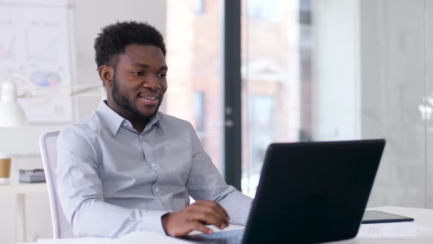 Business, technology and communication concept - happy smiling african american businessman having video chat on laptop computer at office | Shutterstock HD Video #1010257901