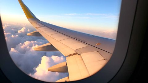 Airplane flight. Wing of an airplane flying above the clouds with sunset sky. View from the window of the plane. Airplane, Aircraft. Traveling by air. 4K UHD video