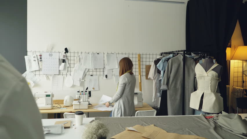Female fashion designer is choosing and hanging clothing sketches to wall for her newest collection. Light fabrics, clothes hanging and sewing items are visible. | Shutterstock HD Video #1010290301