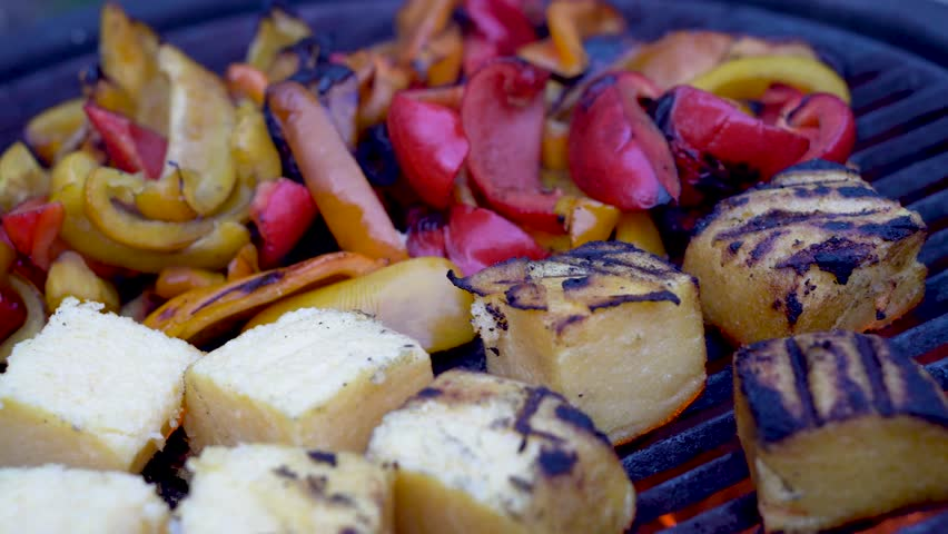 Slider to the right browning polenta on the grill with roasted peppers in the distance.