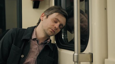 man sleeping in a underground Metro subway train. Tired worker student sleep after work, hard day, illness, fatigue, tiredness,