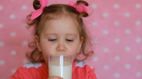 The child drinks a milk. A nice little girl holding a glass with drink in her hands and drinking.