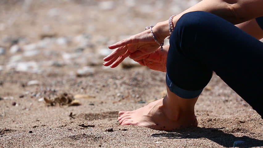 Woman sitting on beach sand and tickling- cleaning her feets from sand