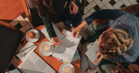 Top view of female college students with books and notebooks studying together at coffee shop