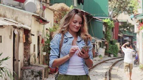 A young traveler woman smiling and using app on smartphone, stay on the old city, by rail road. Vietnam, Hanoi city, Train street.