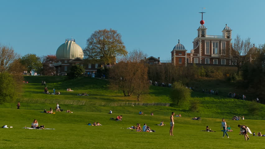 LONDON, circa 2018 - Wide angle shot of city dwellers enjoying a fine Summer day out in Greenwich Park and Royal Observatory in London, England, UK