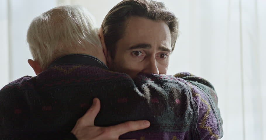 The last farewell to an adult son with an old father near the window. Strong emotional scene.