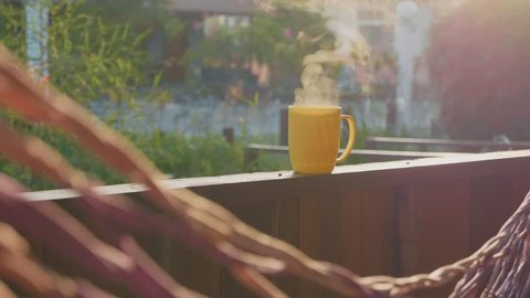 Steaming hot yellow cup of tea on the terrace with swinging hammock on foreground with no people, slow motion