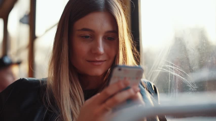Portrait of attractive smiling girl in train using smartphone chatting with friends woman hand internet technology cellphone city mobile phone smartphone tram female transport young slow motion