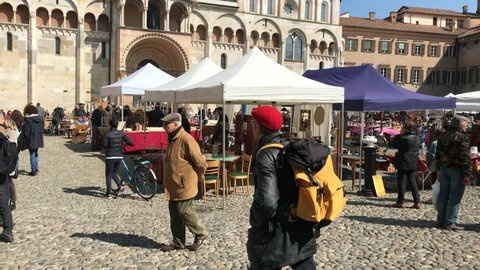 Modena, Italy - 03 24 2018: people walk in the main square during the Sunday market