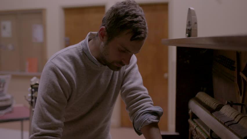 Musician thinking while playing piano HD stock video. Alexa camera