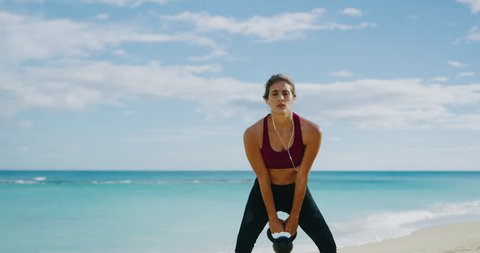 Athletic woman working out with kettlebells