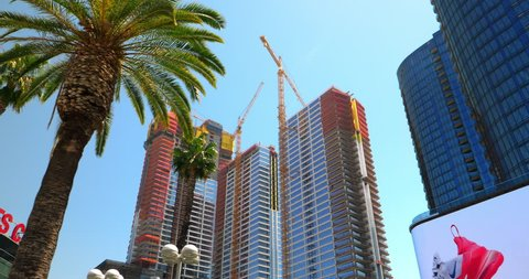LOS ANGELES, CALIFORNIA, USA - APRIL 22, 2018: Construction boom at development site near famous NBA Staples Center and electronic digital billboards in Los Angeles Downtown, California, USA, 4K
