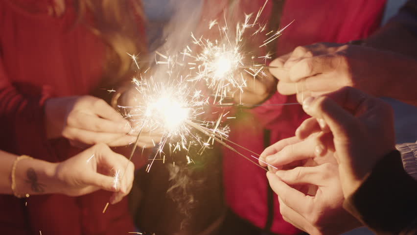Group of friends celebrating holding sparklers on beach enjoying new years eve beach party at sunset real people series | Shutterstock HD Video #1010551091