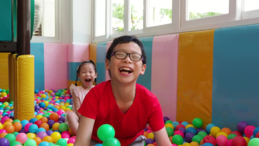 Asian siblings playing in colorful balls pool   Shutterstock HD Video #1010583551