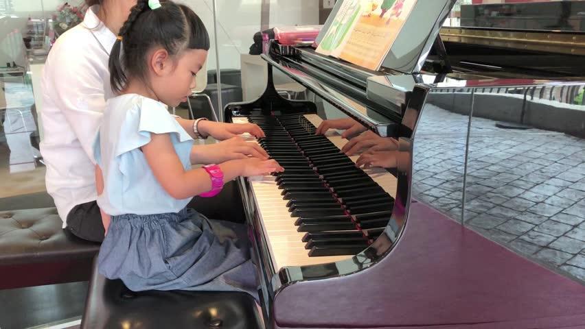 Little child is learning piano for beginner. Sitting next to teacher. Filmed on April 24, 2017 in Bangkok, Thailand.