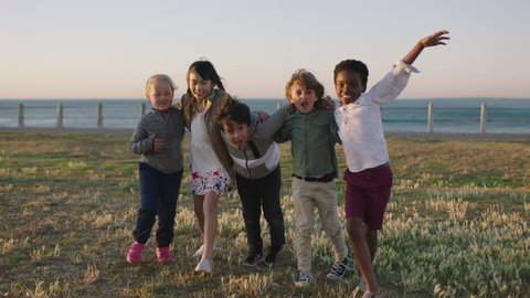 happy lively kids portrait of excited children group embracing celebrating enjoying seaside beach fun at sunset
