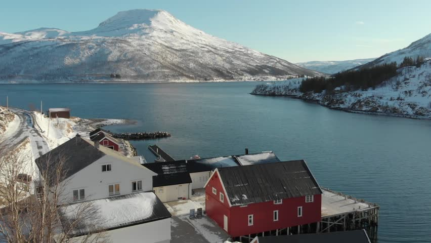 Aerial view of fjord located at Tromso, Norway during winter time with typical Norwegian wooden cottages by the coast.