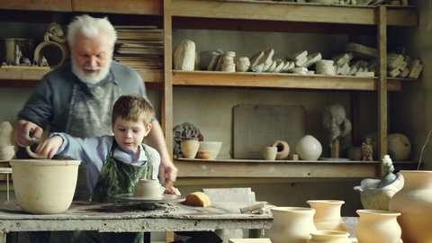 Cute boy is molding clay on throwing wheel while his caring grandfather is teaching and helping him, giving advices. Shelves with numerous ceramic pots in background.
