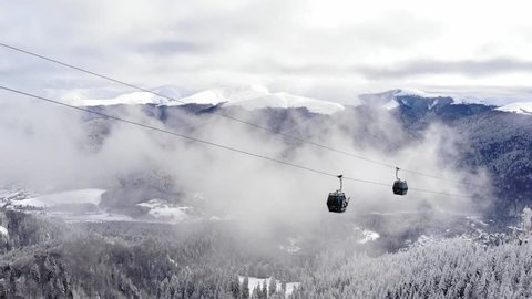 Aerial view over snowy mountain ridge valley with clouds, cable car lifting. Outdoor snow alpine wild nature tourist gondola transportation in winter. High altitude gondola in winter. Ski Gondola