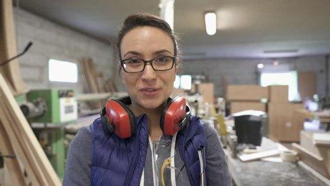 Woman in wood workshop talking to camera