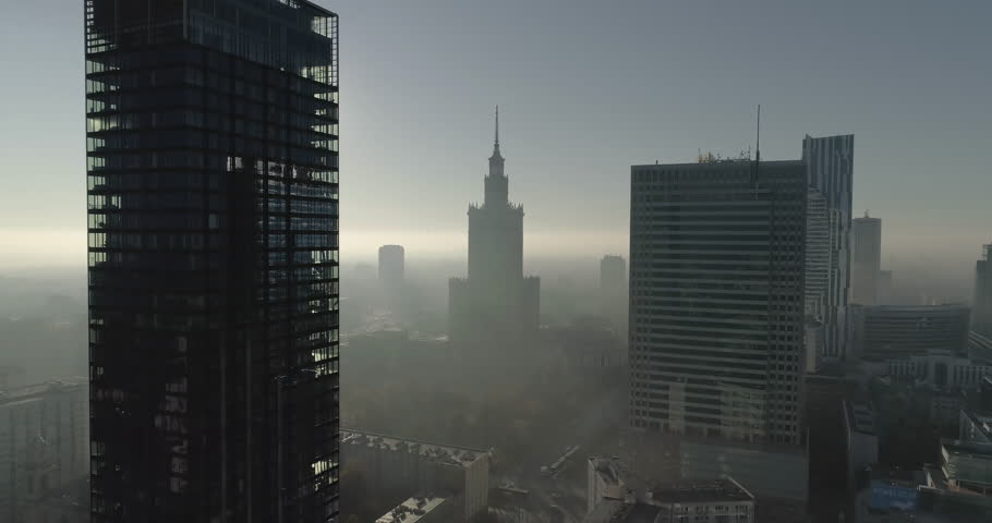 Drone footage in between office skyscrapers towards the Palace of Culture and Science. Shot is taken during a misty but sunny day in Polish capital city, Warsaw.