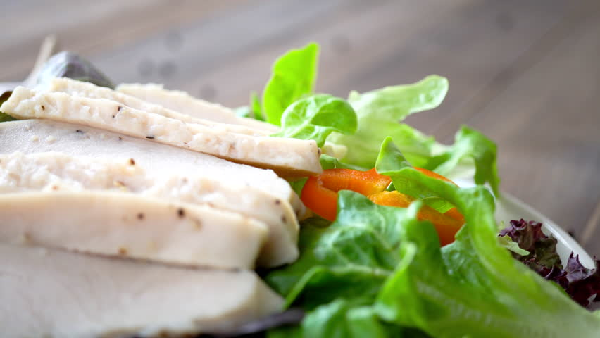 Colorful fresh homemade healthy salad with boiled chicken breast, closed up dolly shot