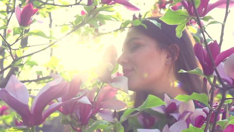 Beauty young woman enjoying nature and touching spring magnolia flowers, Happy Beautiful girl in Garden with blooming magnolia trees. Model smelling blossom, slow motion