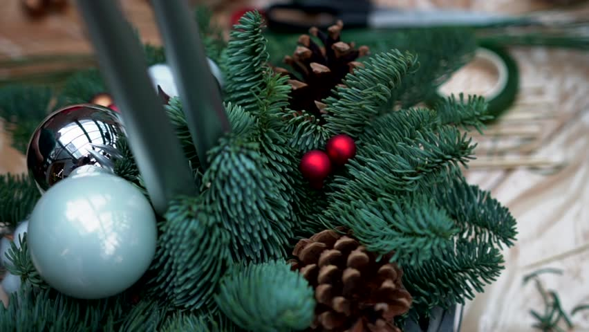 Christmas arrangement: pine tree, pine cones, taper candles, christmas tree toys and cotton flower balls in wicker basket on plastic wrap, close-up.