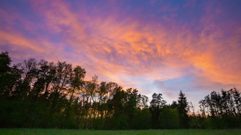 Beautiful sunset sky over forest and meadow in 4K timelapse. 3840x2160, 30fps.