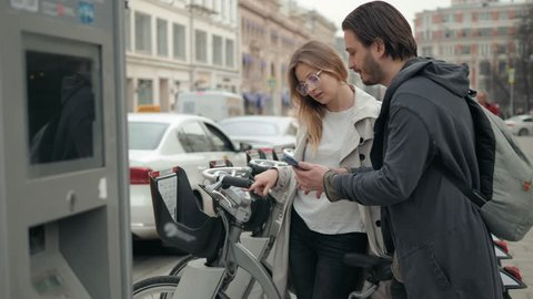 Happy romantic couple of tourists taking bikes for rent in city street, use phone application and credit card, man and woman rent bycicles