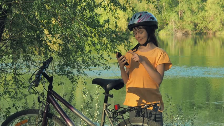 Child on the nature on the Internet. Girl on a bicycle with a phone. | Shutterstock HD Video #1010730641