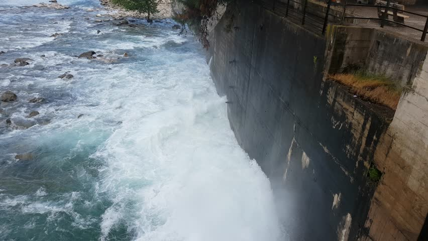 Spring flood water flowing on hydroelectric power station dam | Shutterstock HD Video #1010763641