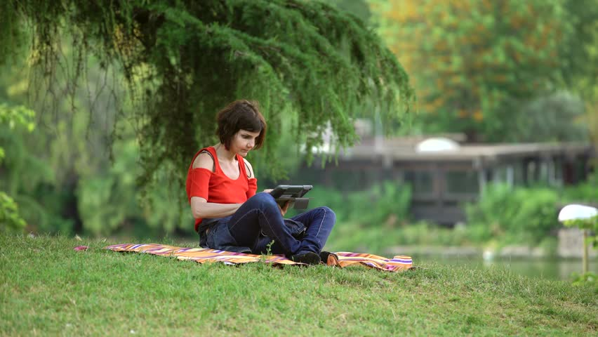 Portrait of gorgeus and relaxed  woman sitting on the lawn uses digital tablet  | Shutterstock HD Video #1010789861