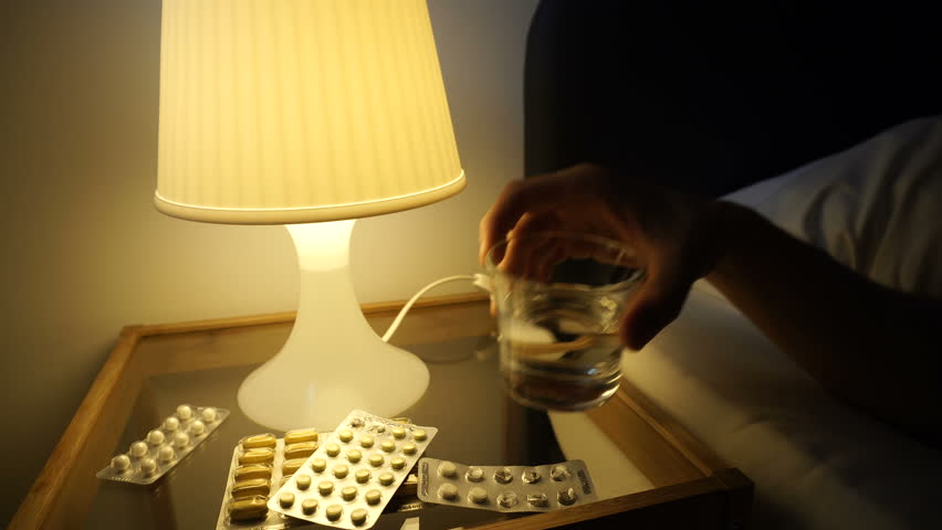 A lot of medications pills tablets on bedside table. Sick man sleep in bed, switch on night lamp, take glass of water, drink, turn off light. Self-medication concept. Filmed 4K Sony a6300.