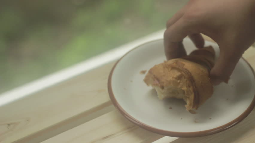 Eaten croissant being putted back onto a plate