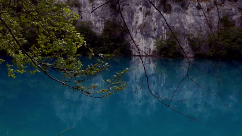 Right to left pan in the crystal clear blue water lake of Plitvice Lakes National Park with trees in foreground and rock cliff in background  | Shutterstock HD Video #1010797931