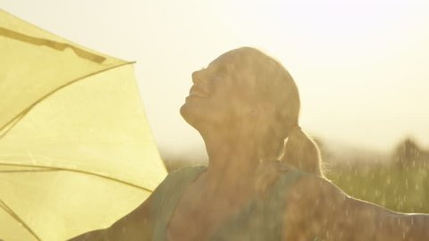 SLOW MOTION, CLOSE UP: Carefree young blonde woman lets the refreshing spring rain fall down on her. Cheerful girl in green sundress puts her umbrella to the side and dances in the cool summer rain.