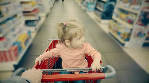 Little child sits in a trolley, yawns, his parent rolls along shelves with goods in the store