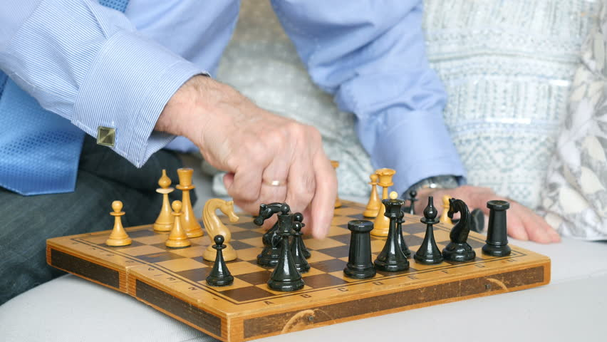 Close-up, hands of an elderly man playing chess with himself
